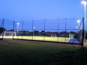 astroturf pitch under flood lights